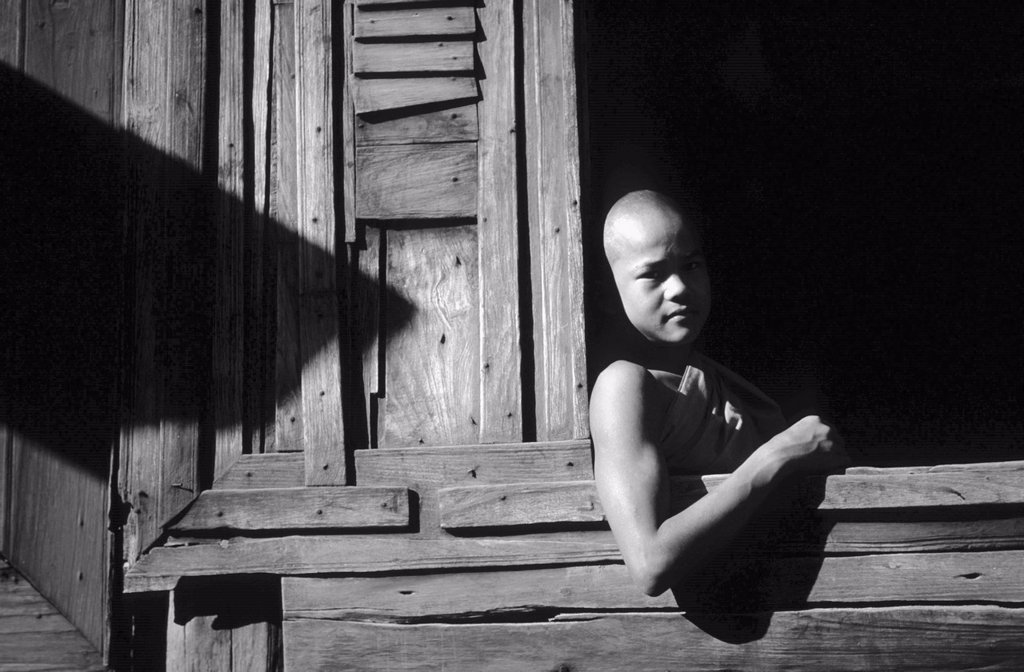 Stock Photo: 1566-1105012 Young Buddhist monk at the window of a wooden monastery in Bagan