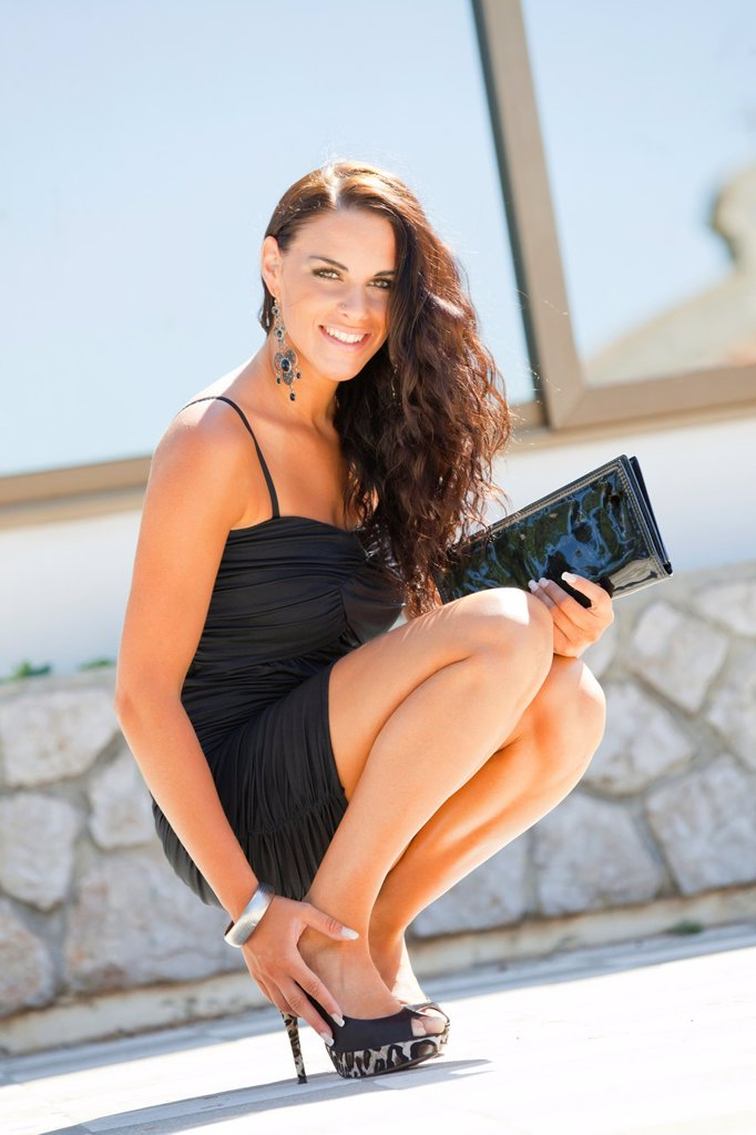 Stock Photo: 1566-1105271 Attractive young woman fanciful in a Black dress squatting