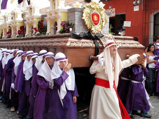 Purple robed youth group carrying heavy float with brotherhood member in front : Stock Photo