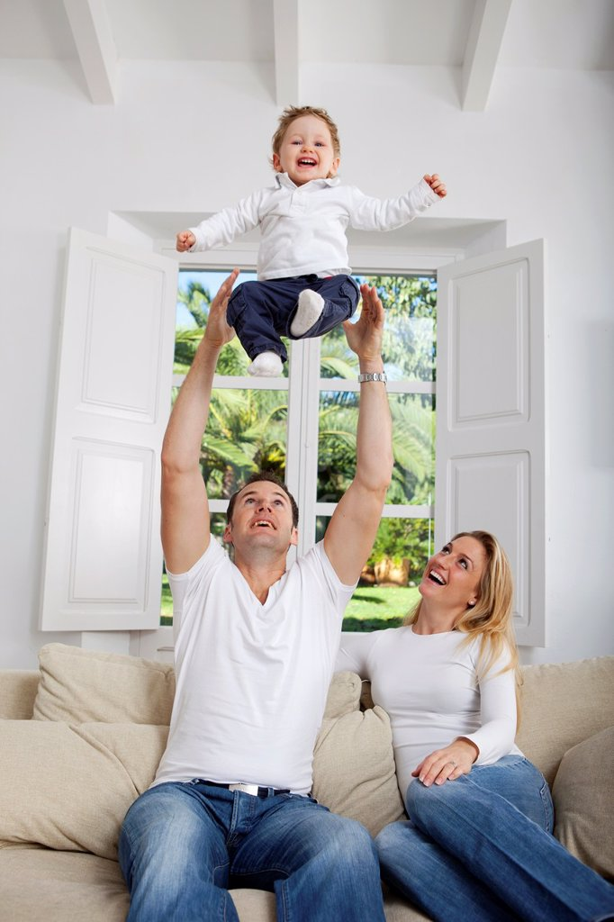 Family on their sofa throwing one year old baby in the air : Stock Photo