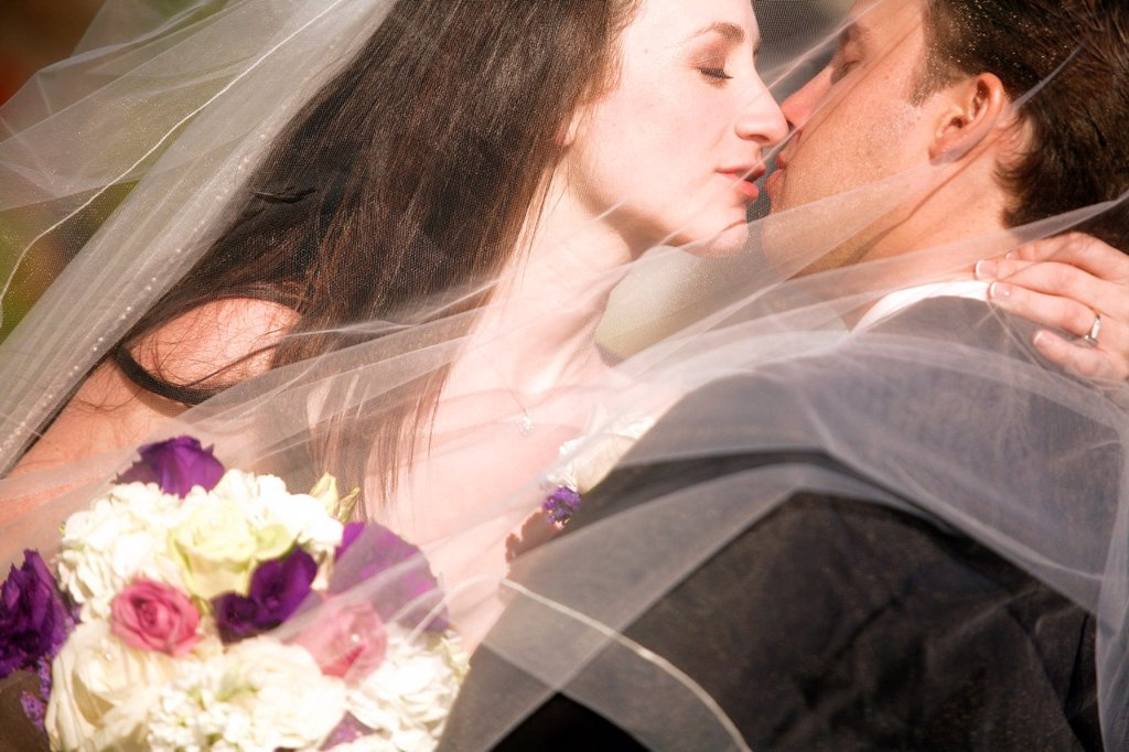 bride groom kissing embracing after wedding behind her wedding veil : Stock Photo