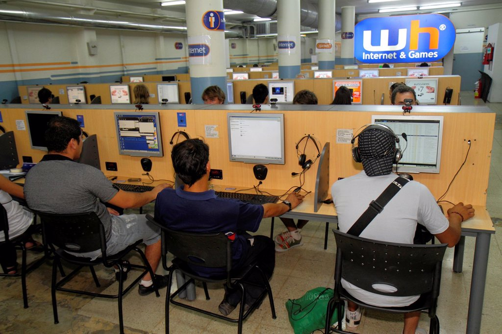 Stock Photo: 1566-1123827 Argentina, Mendoza, Avenida San Martin, WH Internet & Games, business, Internet cafe, cybercafe, paid access, fee, computer terminal, earphnoes, mouse, keyboard, Hispanic, man, busy, customer,