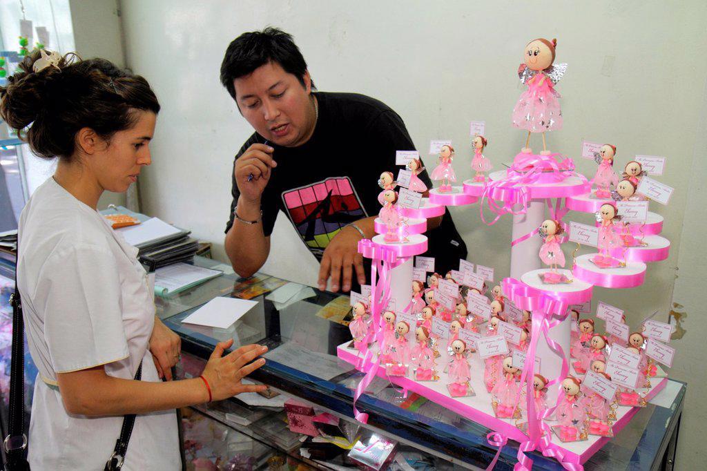 Argentina, Mendoza, Avenida San Juan, shopping, store, business, party goods, retailer cake toppers, figurines, decorations, Hispanic, woman, man, sales clerk, customer, : Stock Photo