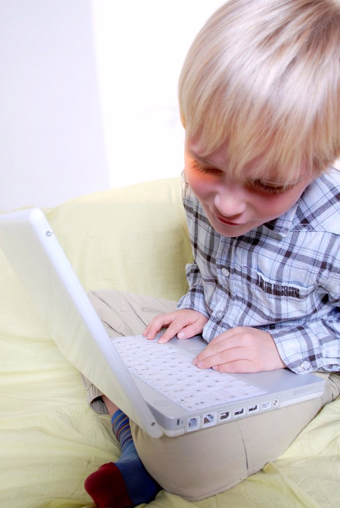 Laptop use  Boy using a laptop computer : Stock Photo