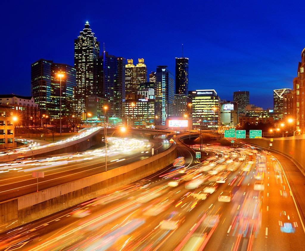 Stock Photo: 1566-1128490 Skyline view of Atlanta, Georgia with rush hour traffic in foreground at dusk.