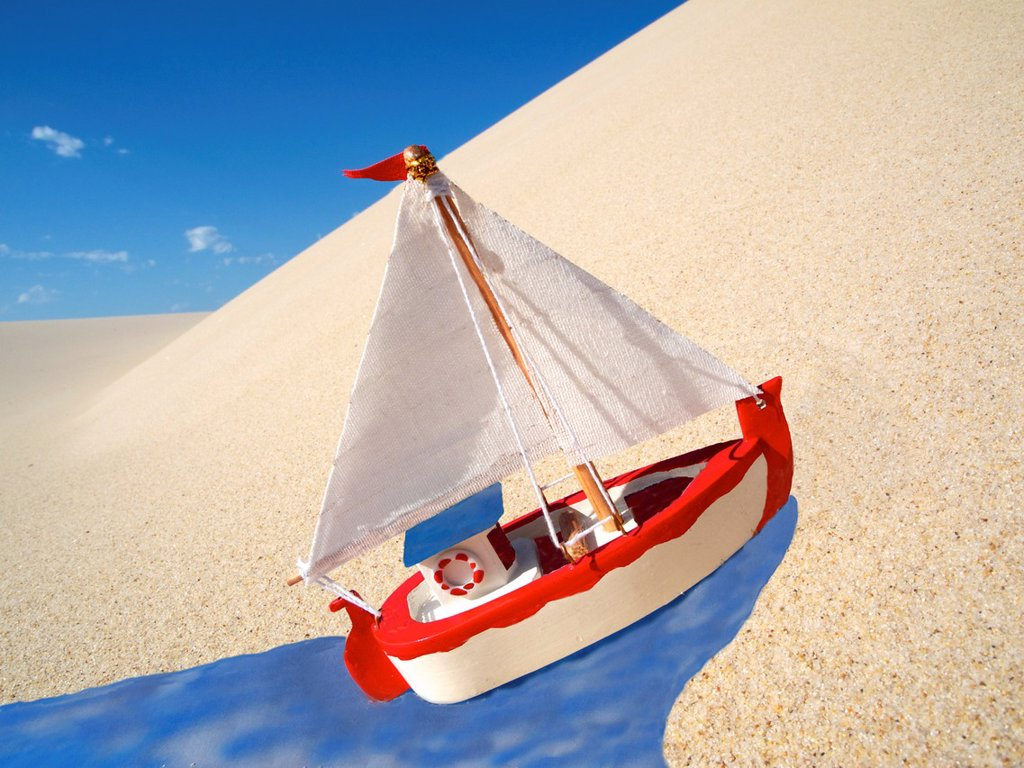 tiny sailboat sailing up dune on paper water : Stock Photo