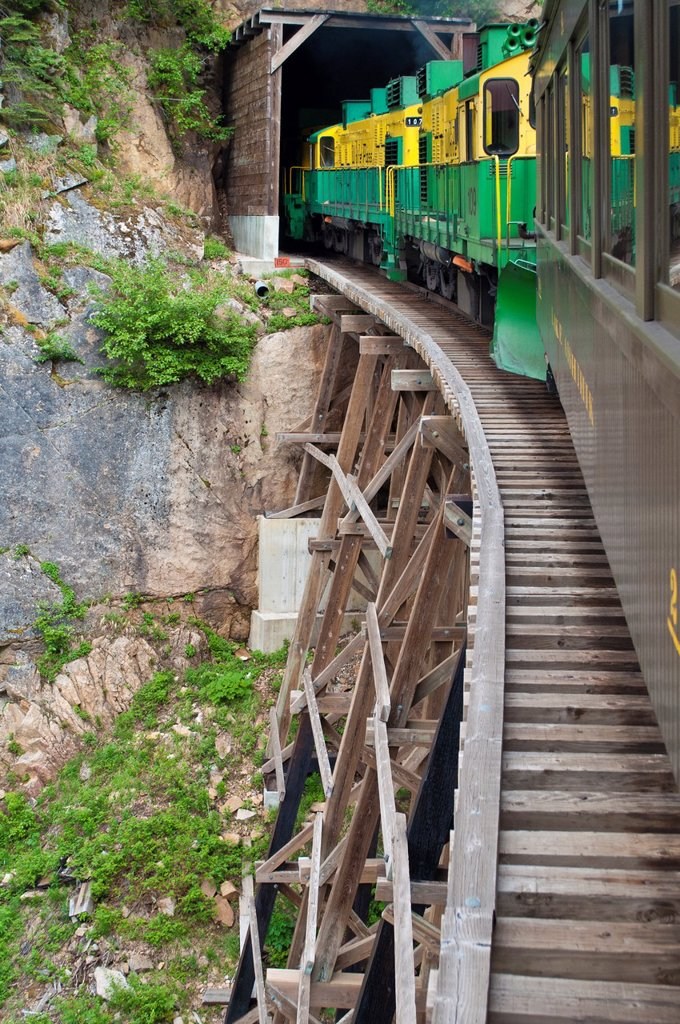 Stock Photo: 1566-1131657 A sightseeing train crosses a precarious trestle to enter a tunnel along Alaska´s White Pass