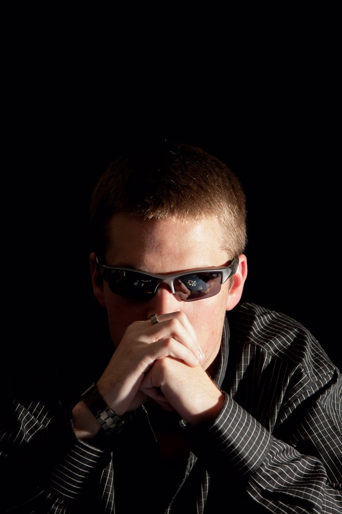 Reflection of cards and poker chips in the sunglasses of a young adult gambler : Stock Photo