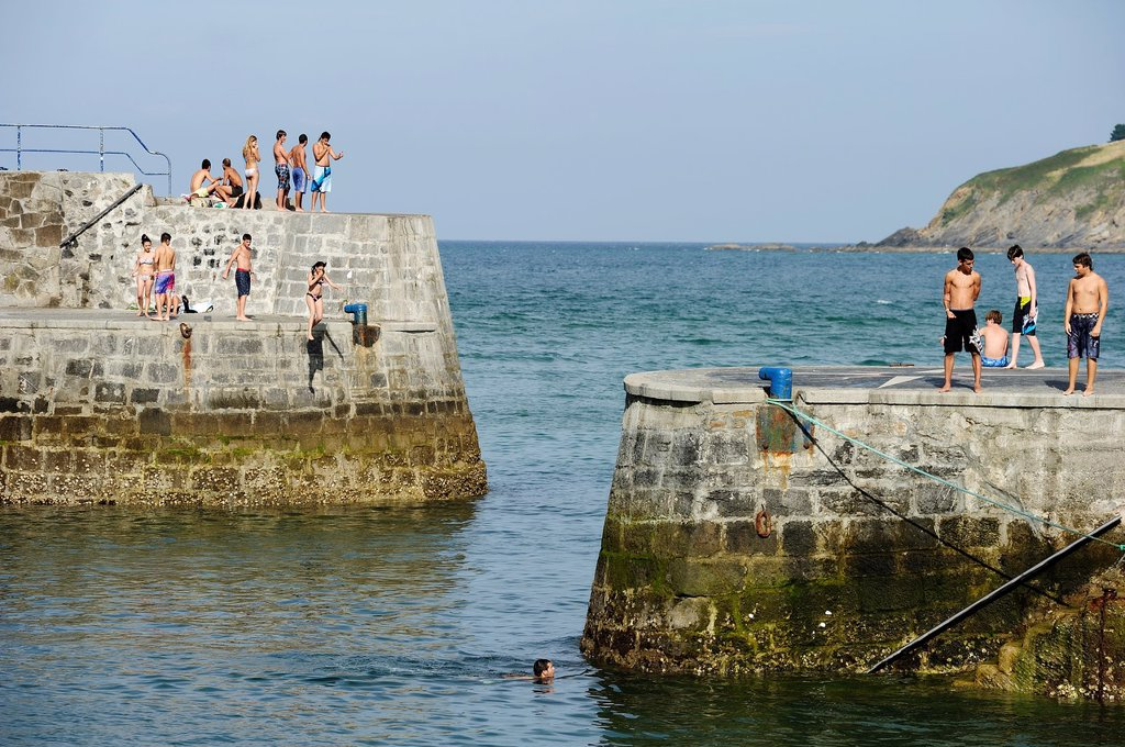 Young people jumping and swimming in the harbor, Mundaka, Biscay, Basque Country : Stock Photo