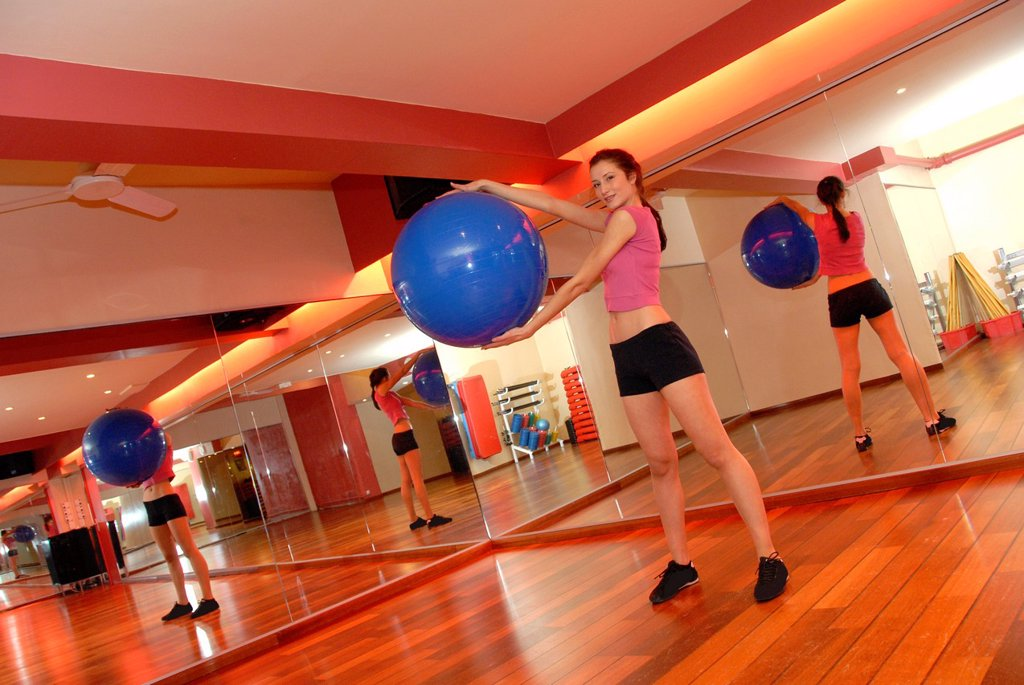 Woman using an exercise ball in a gym  These balls are used when exercising because their inherent instability causes more of the body´s muscles to respond to maintain balance, thus providing a better work-out : Stock Photo