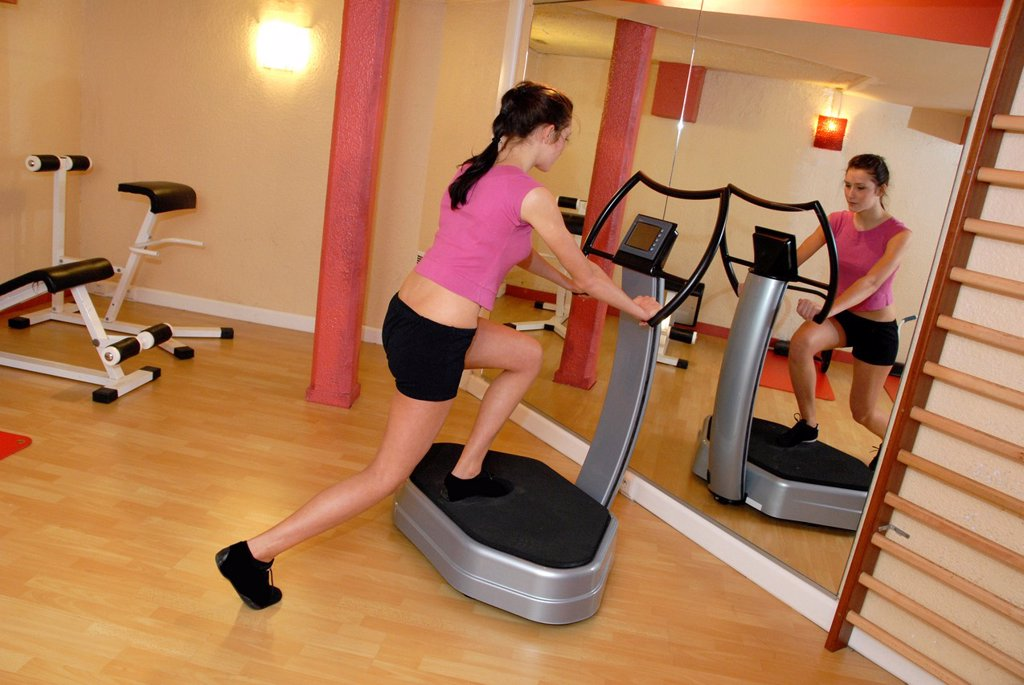 Stock Photo: 1566-1137218 Woman exercising on machine in gym