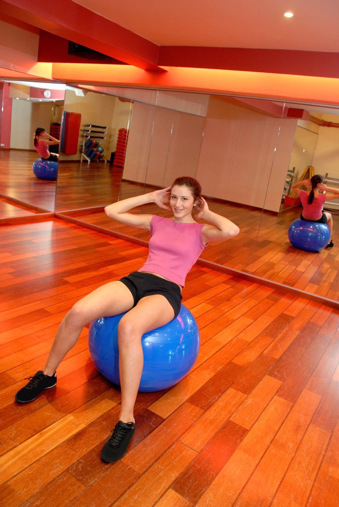 Stock Photo: 1566-1137226 Woman using an exercise ball in a gym  These balls are used when exercising because their inherent instability causes more of the body´s muscles to respond to maintain balance, thus providing a better work-out