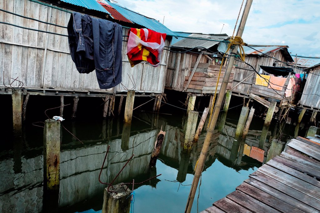 Washed clothes of the shellfish pickers hang on the line in a stilt house area close to Tumaco, Colombia, 11 June 2010  Deep in the impenetrable labyrinth of mangrove swamps on the Pacific seashore, hundreds of people struggle everyday, searching and gath. Washed clothes of the shellfish pickers hang on the line in a stilt house area close to Tumaco, Colombia, 11 June 2010  Deep in the impenetrable labyrinth of mangrove swamps on the Pacific seashore, hundreds of people struggle everyday, search : Stock Photo