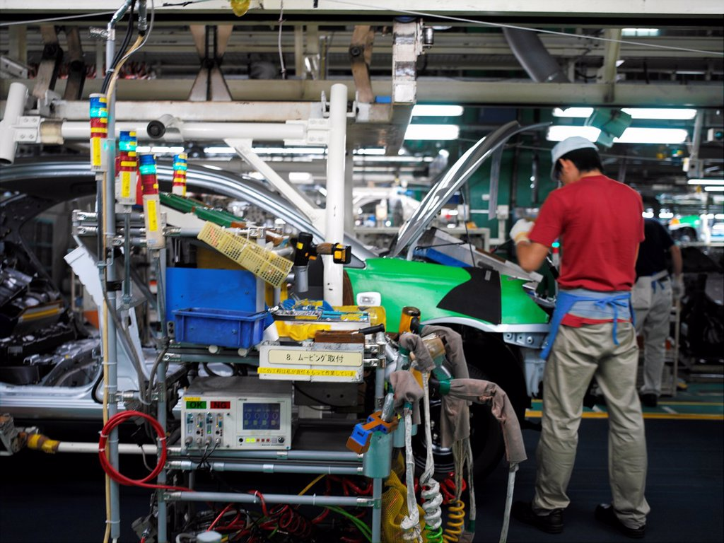 Stock Photo: 1566-1142365 Factory workers producing Toyota cars and vans, work on the assembly line at the Toyota City factory in Japan. This is also where the Toyota Prius is assembled.