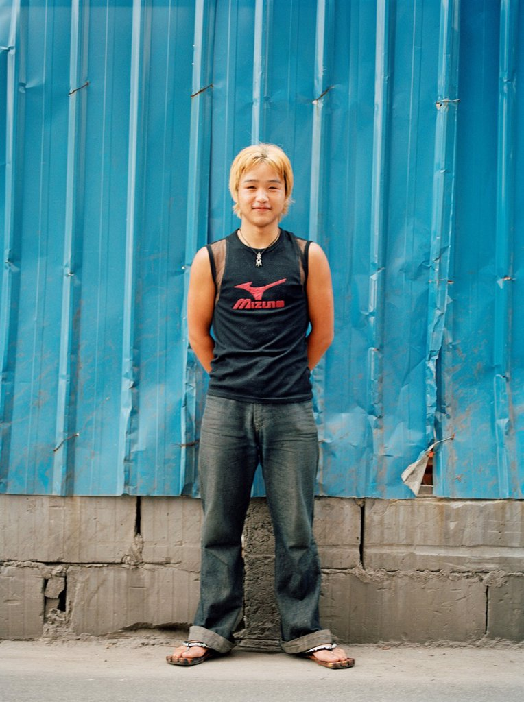 Stock Photo: 1566-1142648 A young Chinese teenager wearing jeans with bright yellow dyed hair and dark black roots standing in front of a blue, metal partition He represents the new and liberal China