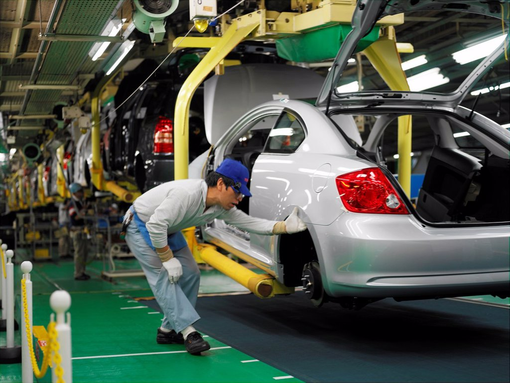 Stock Photo: 1566-1142999 Factory workers producing the hybrid Toyota Prius cars, work on the assembly line at the Toyota City factory in Japan. Here a Scion TC is being inspected.