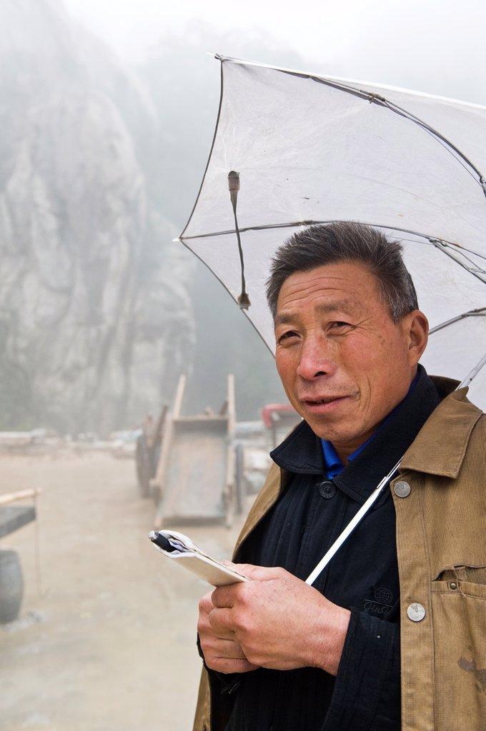 Stock Photo: 1566-1144183 A foreman with an umbrella overseas work at the San Huang Zhai Monastery on the Song Mountain, China