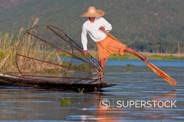 Stock Photo: 1566-1148212 Myanmar, Burma  Fisherman Looking for a Place to Set his Net, while rowing with one leg, in the style common to Inle Lake, Shan State