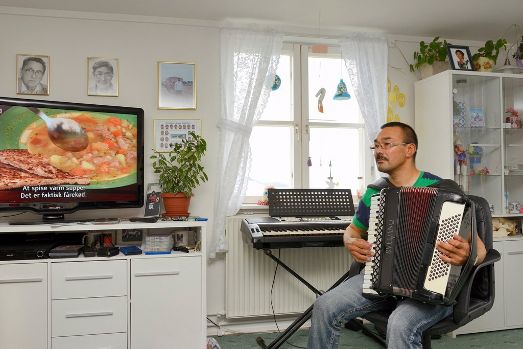 Greenland, Baffin Bay, Tasiusaq, Inuit fisherman Hans Bidstrup at home playing accordion : Stock Photo