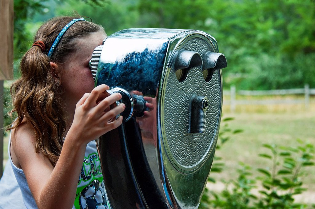 Girl looking through a viewing scope : Stock Photo