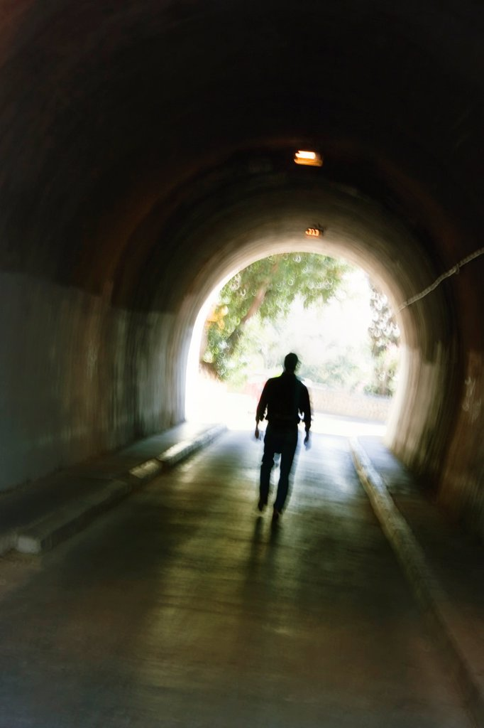 Mysterious blurred male figure walking in tunnel : Stock Photo