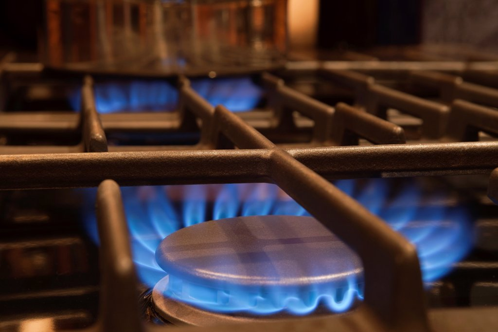 Stock Photo: 1566-1151158 BLUE FLAME OF LIT GAS BURNER RINGS ON STOVE RANGE TOP
