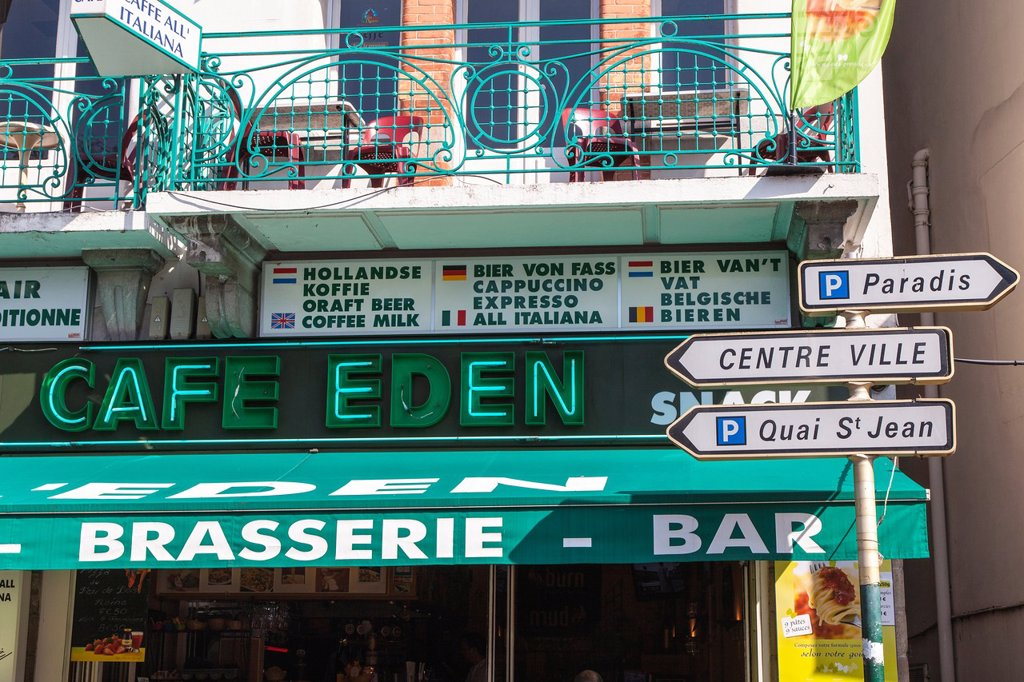 Cafe with faulty neon sign and town sign posts in Lourdes, Hautes Pyrenees, France : Stock Photo