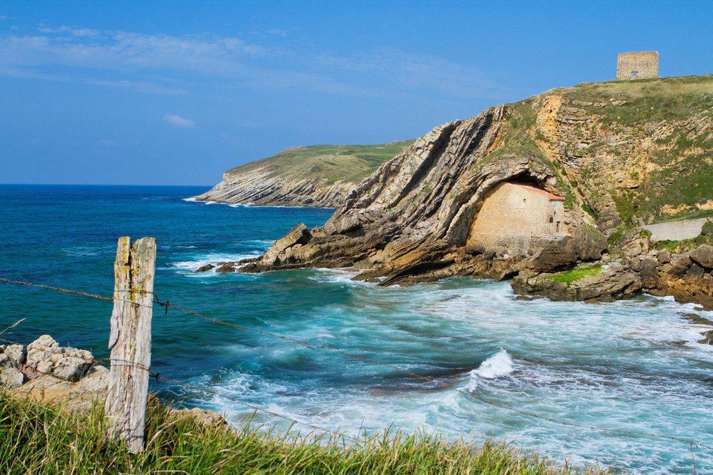 The small Santa Justa Chapel, embedded into the cliff  Santa Justa beach, Ubiarco village  Santillana del Mar  Cantabria  Spain : Stock Photo