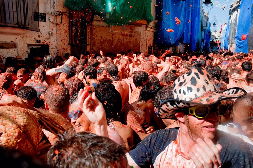 Stock Photo: 1566-1152889 Thousands of people throw tomatoes on the street during La Tomatina festival in Bunol, Spain, 31 August 2006  La Tomatina is a tomato fight held annually in the town of Bunol, close to Valencia  Approximately 40,000 people from all over the world arrive t. Thousands of people throw tomatoes on the street during La Tomatina festival in Bunol, Spain, 31 August 2006  La Tomatina is a tomato fight held annually in the town of Bunol, close to Valencia  Approximately 40,000 people from all over the wo