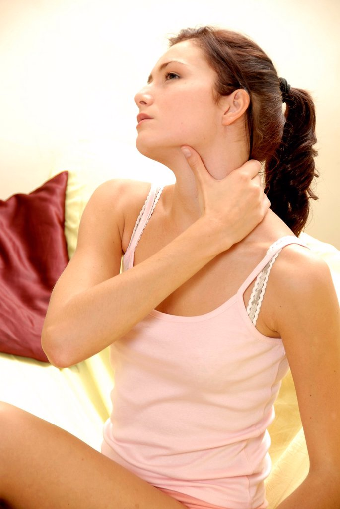 Young woman holding her painful or stiff neck : Stock Photo