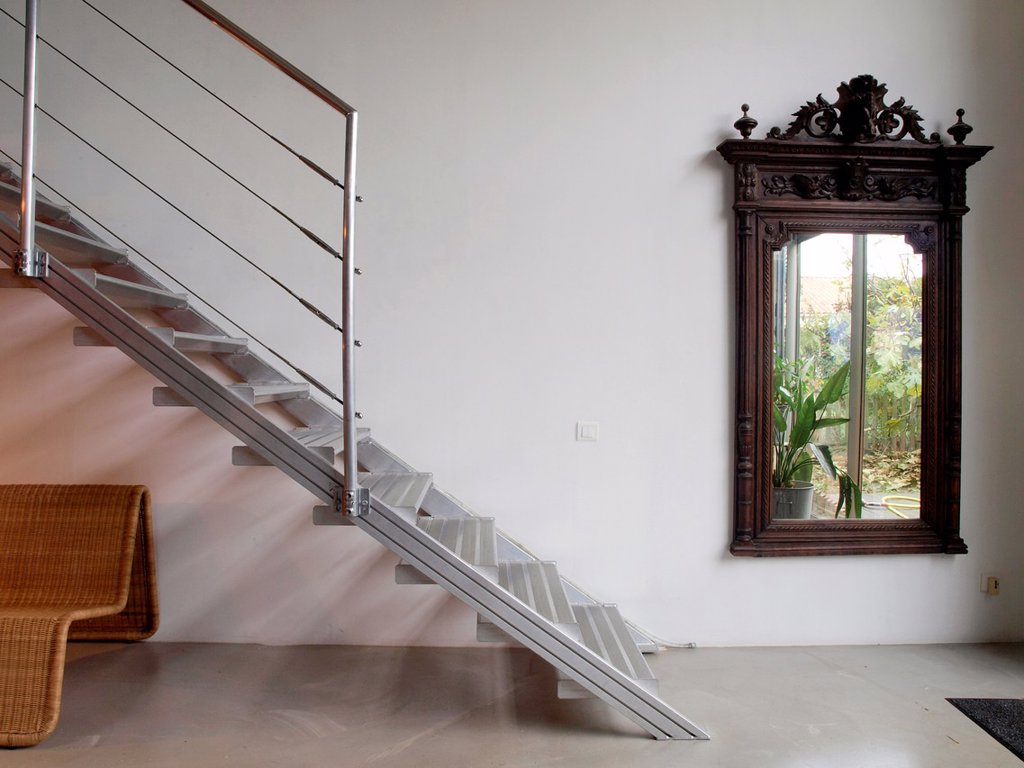 Big wooden mirror. Metallic staircase. Cane armchair. Interior designed by Gabriel Rodriguez. : Stock Photo