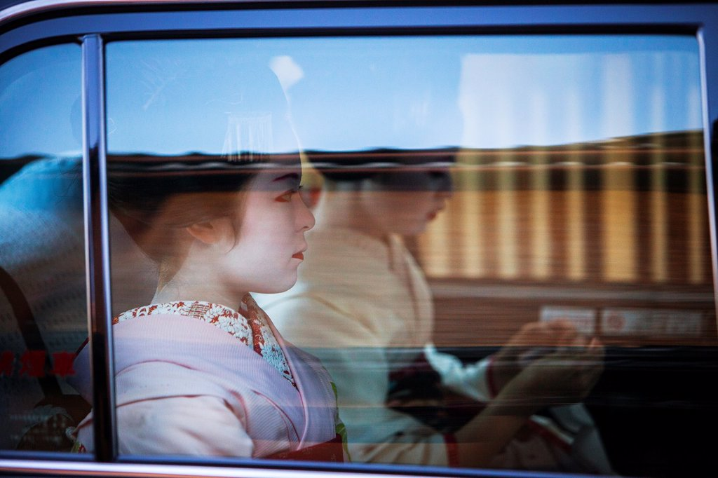 Stock Photo: 1566-1159721 Maikos geisha apprentice in taxi  Hanamikoji dori street Geisha´s distric of Gion Kyoto  Kansai, Japan