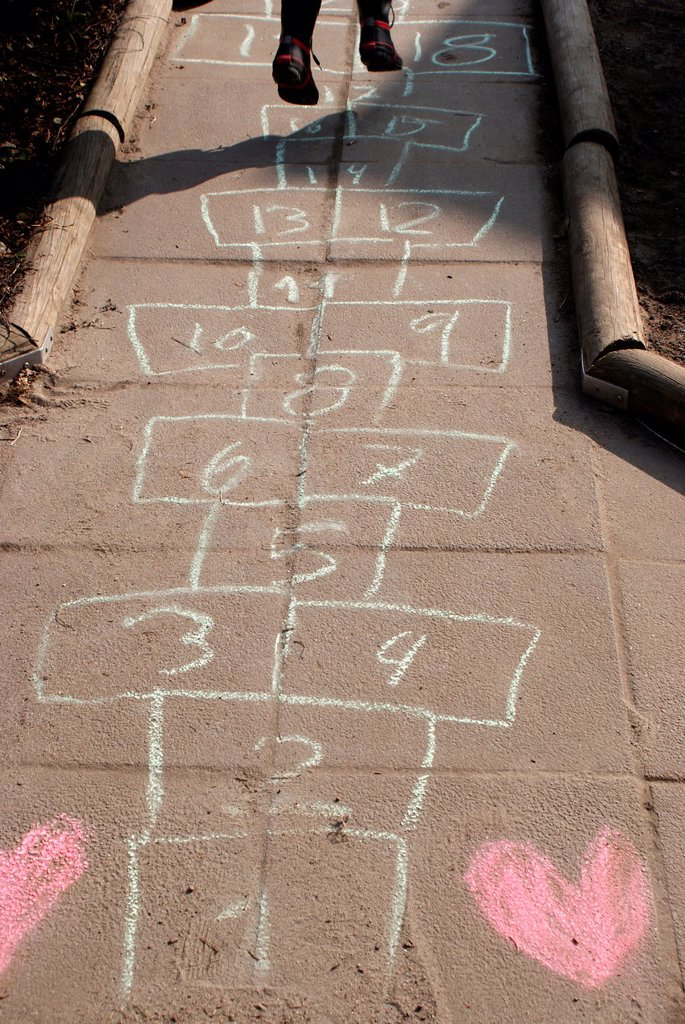 Playing on a hopscotch lane with hearts : Stock Photo