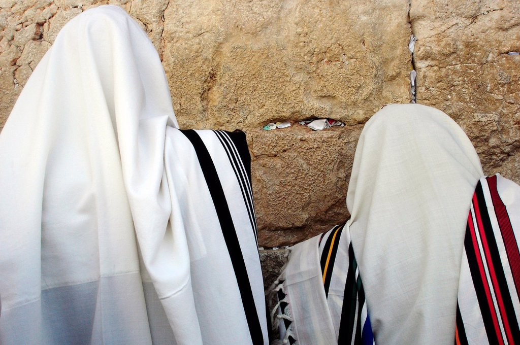 Jewish Men are praying wrapped in talit at the western wall in the old city in Jerusalem, Israel : Stock Photo
