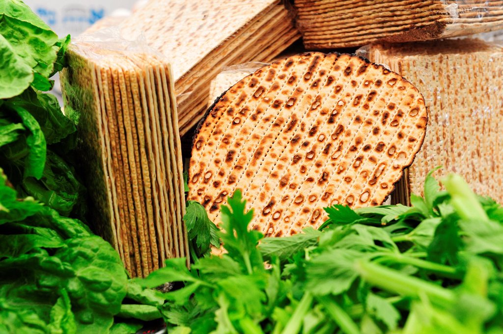 A variety of different types of matza unleavened bread surrounded by green leafy vegetables such as lettuce and celery - traditional food used for blessings on the Jewish religious holiday feast of Passover pesach : Stock Photo