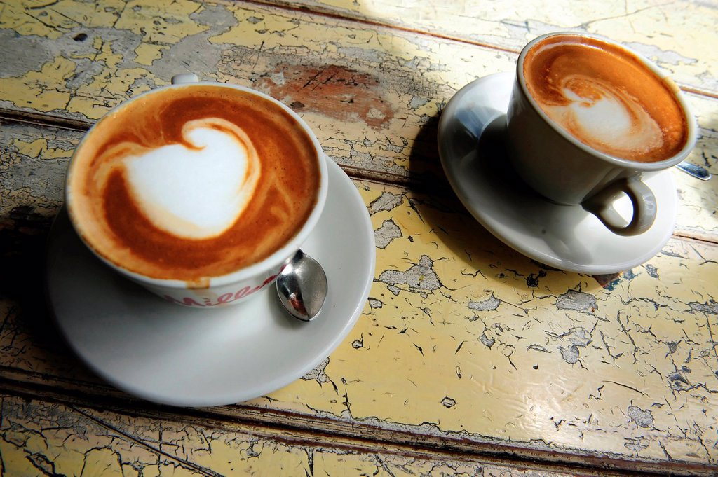Stock Photo: 1566-1160742 Cups of hot flat white coffee drinks on an old wooden table in a cafe