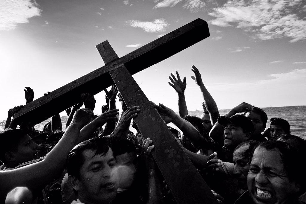 Stock Photo: 1566-1161027 Catholic followers carry the wooden cross in the sea during the annual Holy Week ritual Lavado de la cruz in Santa Elena, Ecuador, 3 April 2012