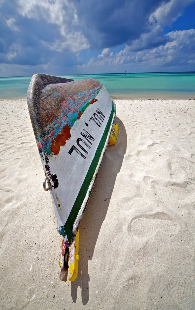Stock Photo: 1566-1164383 Shipwreck of a Wooden Boat on the Coastline of the Turquoise Water of the Carabbean Sea with Storm Clods on the Horizon
