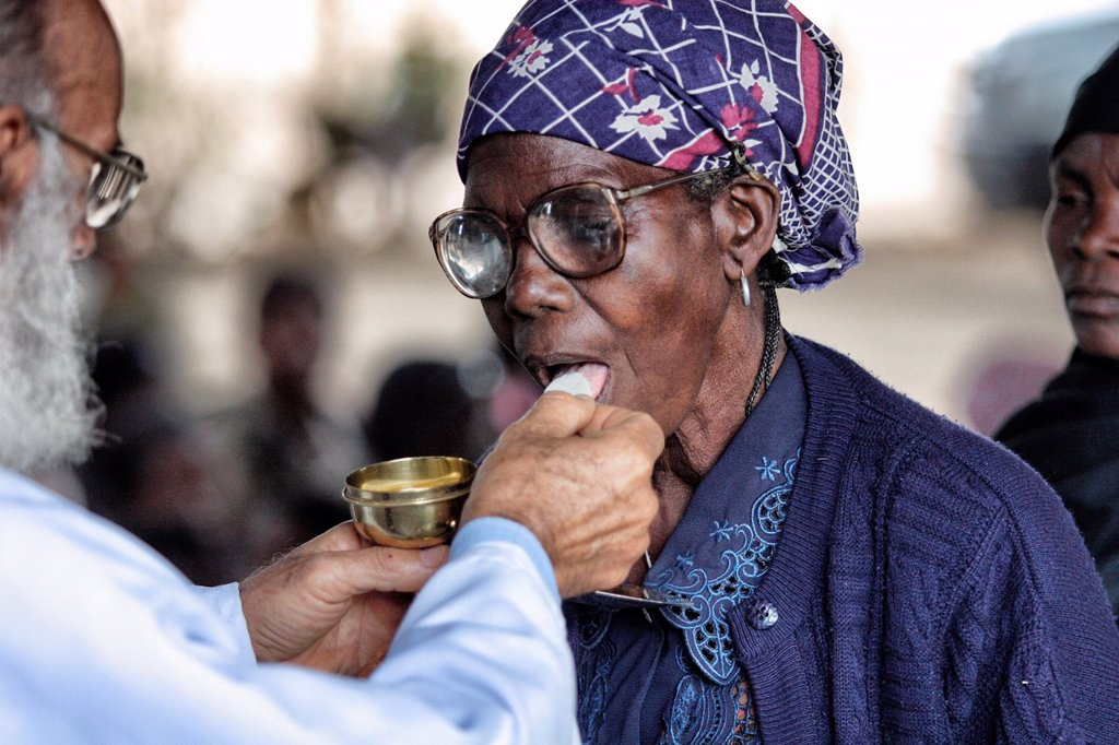 Older woman taking communion from priest in Chalucuane, Mozambique : Stock Photo