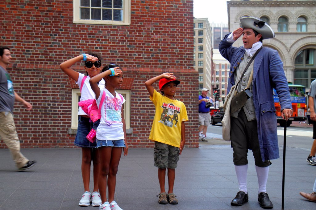 Massachusetts, Boston, Washington Street, The Freedom Trail, Old State House, historic building, costumed re-enactor, actor, man, patriot, Black, boy, girl, student, living history, saluting, : Stock Photo