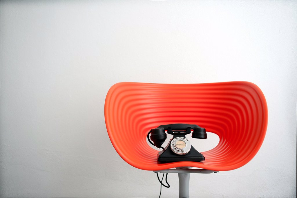 Stock Photo: 1566-1172533 Telefono vintage encima de una silla moderna roja, Vintage telephone on top of contemporary red chair