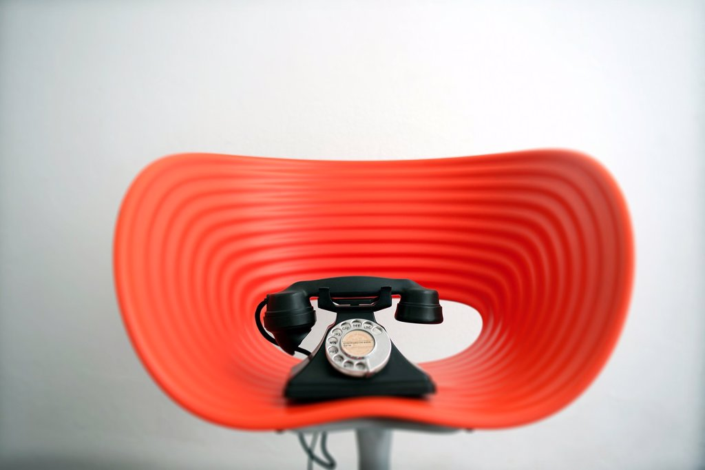 Telefono vintage encima de una silla moderna roja, Vintage telephone on top of contemporary red chair : Stock Photo