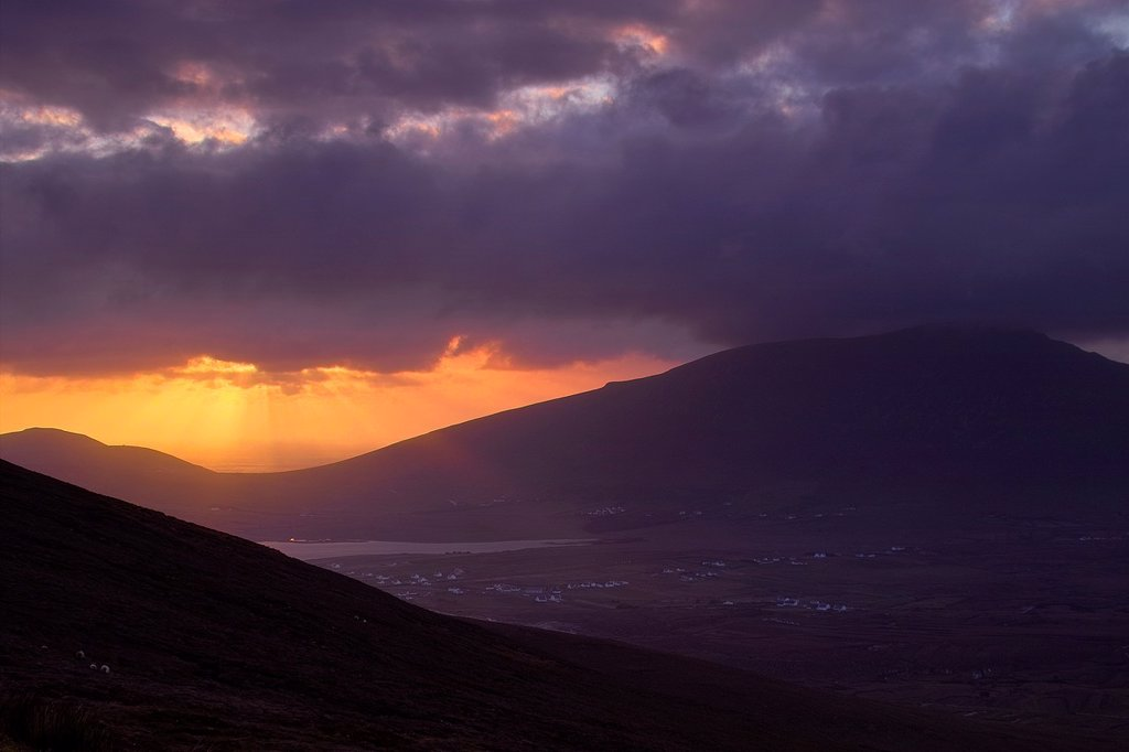 Stock Photo: 1566-1173486 Sunset through stormy clouds, Achill Island, County Mayo, Ireland  Slievemore is seen on the right and Keel village can be seen in the valley