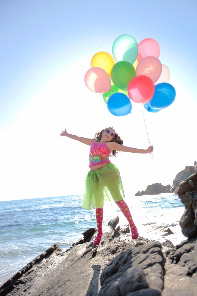 little girl jumping with joy holding balloons while at the ocean : Stock Photo