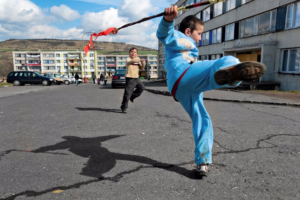 Boys, holding the Easter whips, happily jump in front of an apartment block in the Gipsy ghetto of Chanov, Most, Czech Republic, 26 March 2008 : Stock Photo