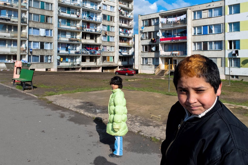 Stock Photo: 1566-1174476 A boy poses for a picture in front of the apartment block in the Gipsy ghetto of Chanov, Most, Czech Republic, 26 March 2008