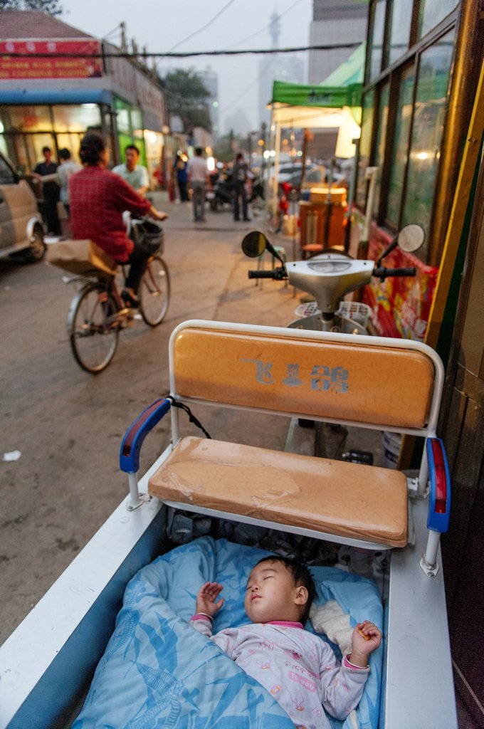 A baby left to sleep alone in the back of a motorcycle wagon : Stock Photo