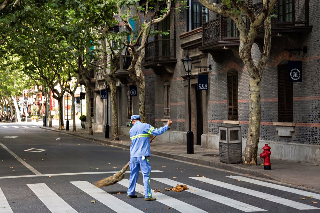 Stock Photo: 1566-1176428 A street sweeper cleans up in Xintiandi Plaza shopping district Shanghai, China