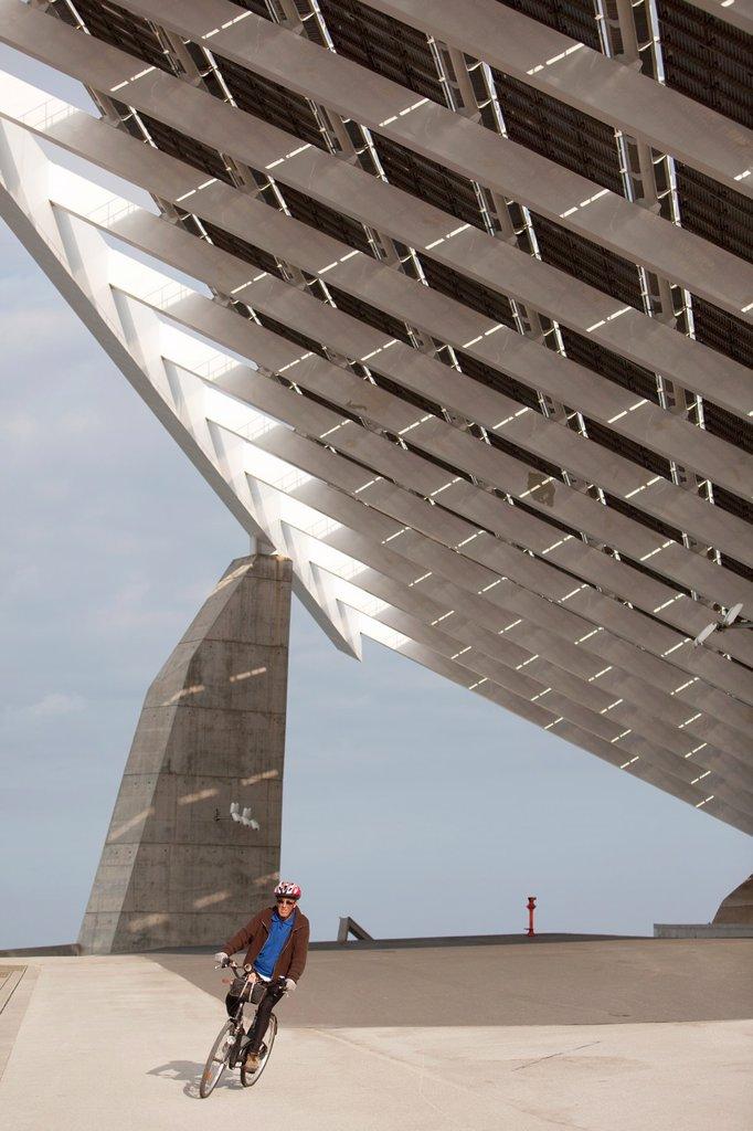 Cyclist under a giant solar panel in Barcelona : Stock Photo