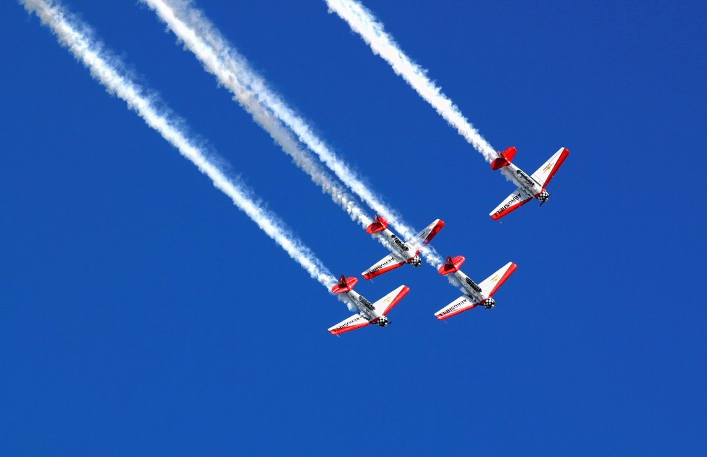 The planes of the Aeroshell demonstration team soar overhead in the blue skies of the Dayton Airshow : Stock Photo